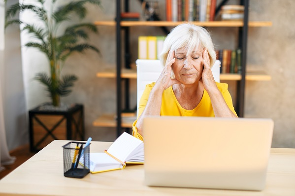 An elderly woman holding head with hands while sitting and working with a laptop indoors.