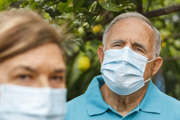 A senior man and woman wear paper facemasks