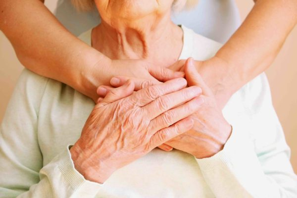 An older woman holding hands with a loved one