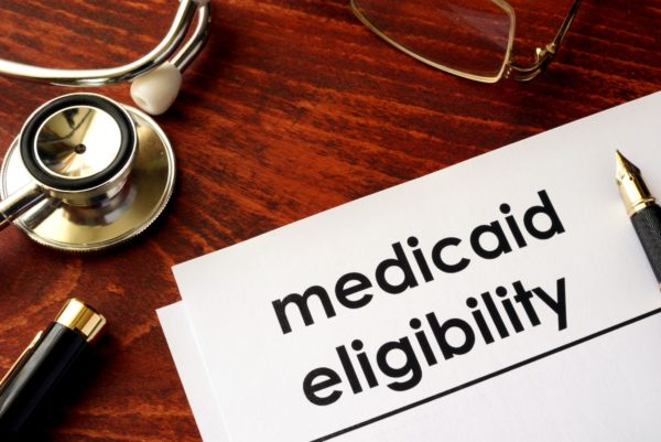 """A piece of white paper on a desk that reads """"medicaid eligibility"""""""