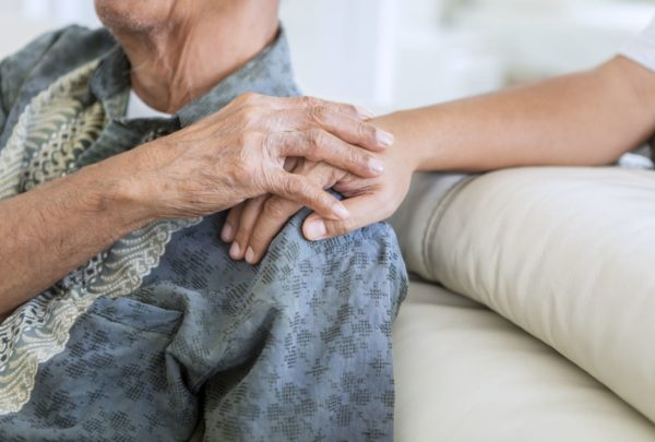 An older person holds hands with a younger person