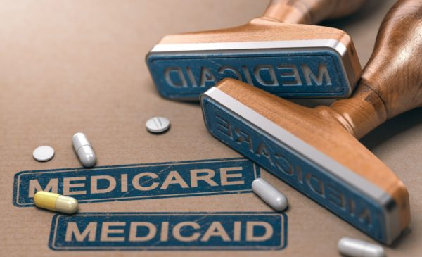 Medicare and Medicaid stampers on a table with prescription pills