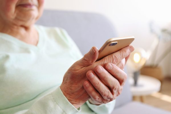 An older woman looks at a cellphone she's holding her hands