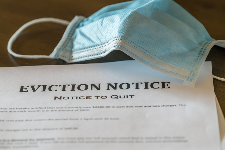 an eviction notice on a table under a paper face mask