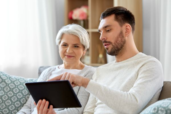 Son sitting next to his mom on a couch, showing her information on a tablet